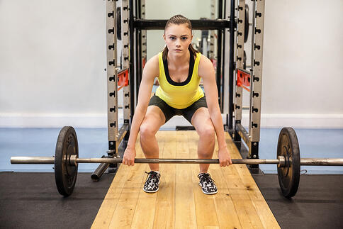Concentrated woman about to lift a barbell and weights at the gym