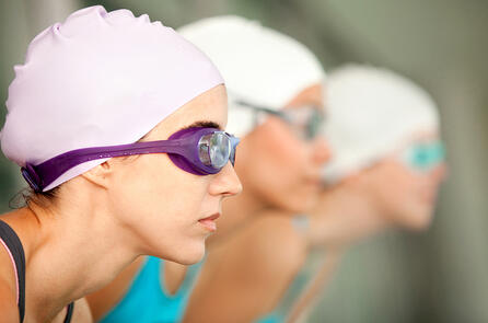 Female swimmers wearing hat and goggles ready to compete